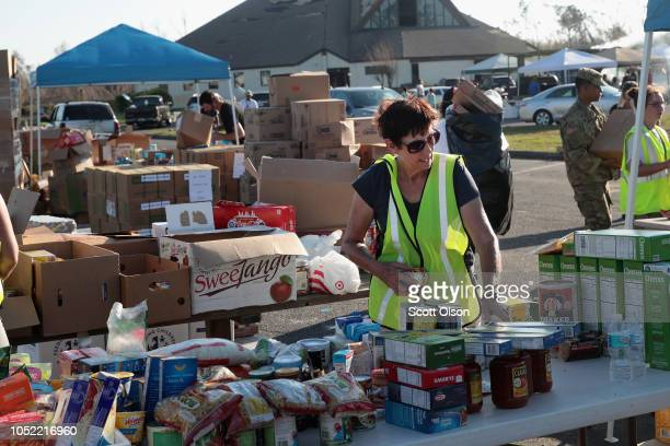 Volunteers help distribute food water cleaning supplies and other necessities to victims of Hurricane Michael at an aid distribution point on October...
