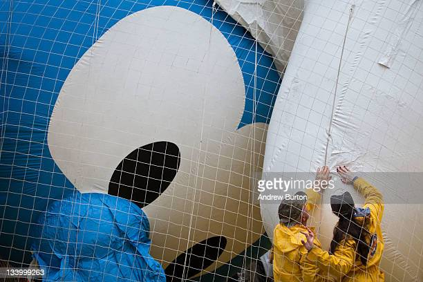 Volunteers help inflate a Smurf flotation for the Macy's Thanksgiving Day Parade on November 23 2011 on West 77th Street in New York City The parade...