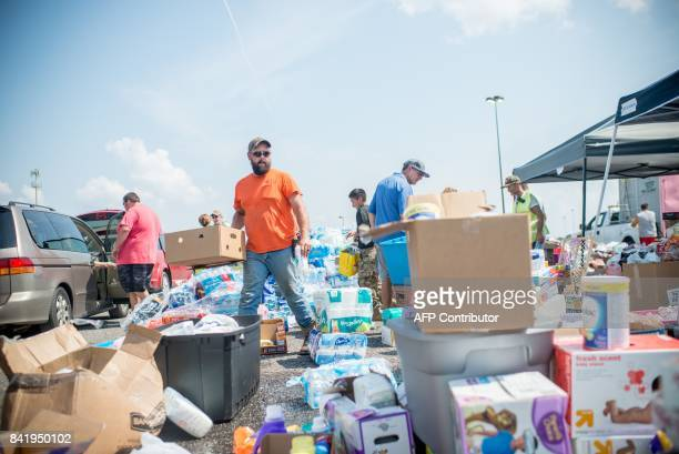Volunteers help load Harvey victims cars with donated supplies outside Center Mall in Port Arthur Texas on September 2 2017 As floodwaters receded in...