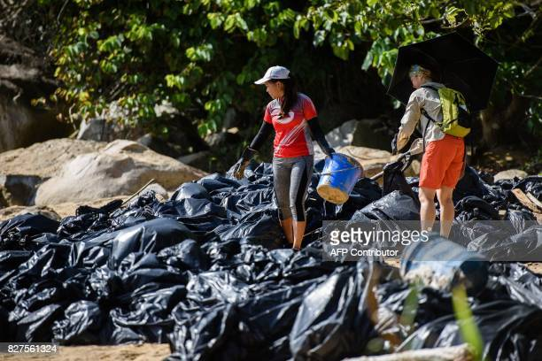 Volunteers help remove washed up palm oil from a beach as they stand amongst a pile of black bin bags on Hong Kong's outlying Lamma Island on August...