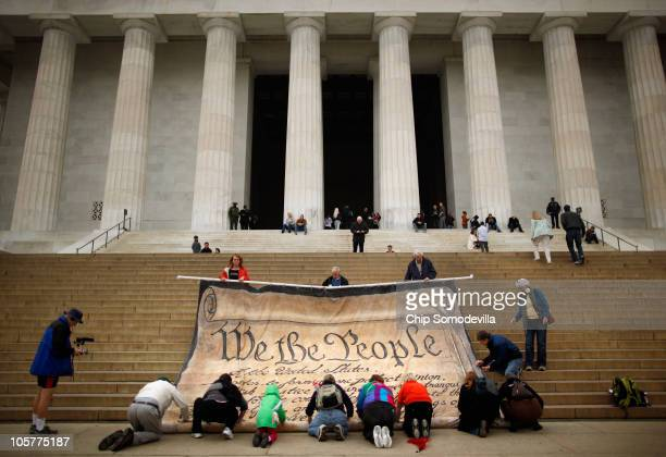 Volunteers help roll up a giant banner printed with the Preamble to the United States Constitution during a demonstration against the Supreme Court's...