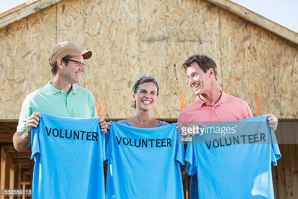 volunteers helping to build homes for the needy - holding aloft stock pictures, royalty-free photos & images