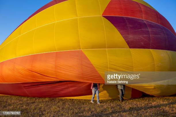 Volunteers helps to inflate a hot air balloon at the Teton Valley Balloon Rally on July 3, 2021 in Driggs, Idaho. The rally has been an annual event...