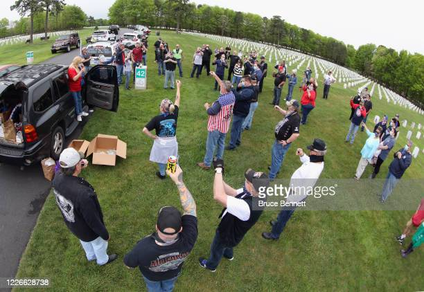 Volunteers hold a brief ceremony while placing flags at the Calverton National Cemetery on May 23 2020 in Wading River New York The US Department of...