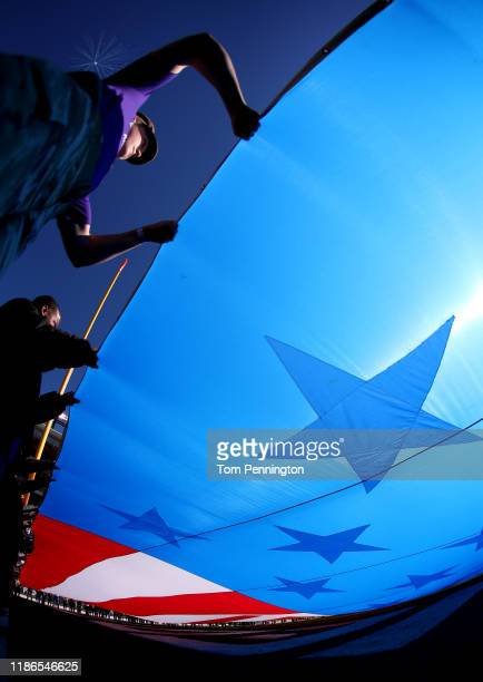Volunteers hold an American flag during the National Anthem before the TCU Horned Frogs take on the Baylor Bears at Amon G. Carter Stadium on...