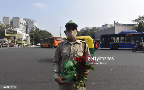 Volunteers hold play cards and flowers at ITO red light to create awareness phase-II, campaign over air pollution control ' Red Light On - Gadi Off'...