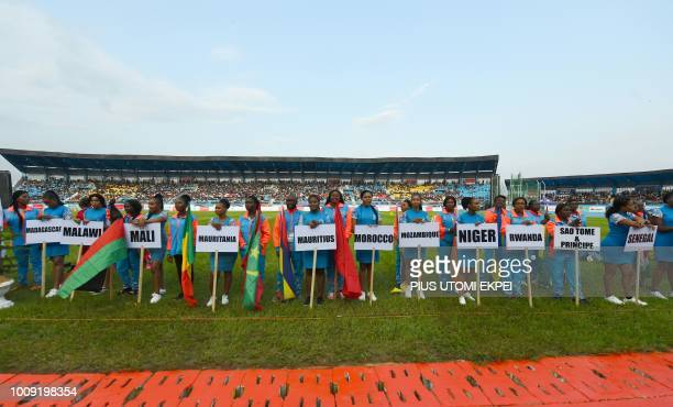 Volunteers hold signs to show participating countries during the opening of the 21st African Senior Athletics Championships at the Stephen Keshi...