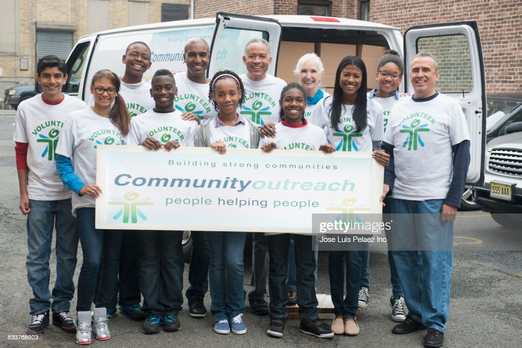 Volunteers holding community outreach banner near delivery van : Foto stock