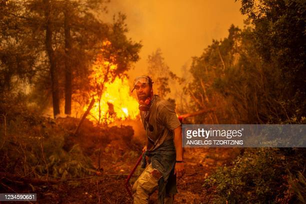 Volunteers holds a water hose near a burning blaze as he tries to extinguish a fire in the village of Glatsona on Evia island, on August 9, 2021. -...