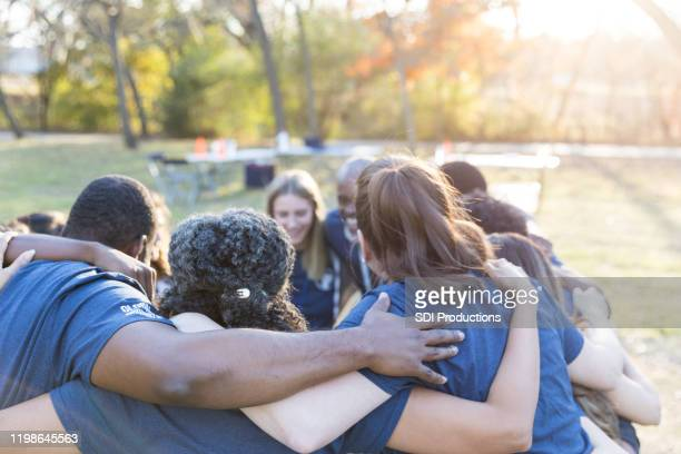 volunteers huddle together, showing unity - huddling stock pictures, royalty-free photos & images