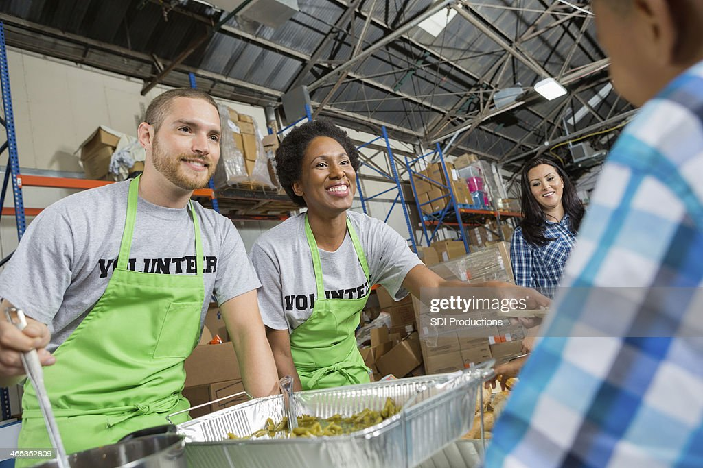 Volunteers in community soup kitchen serving hot meal to families : Stock Photo