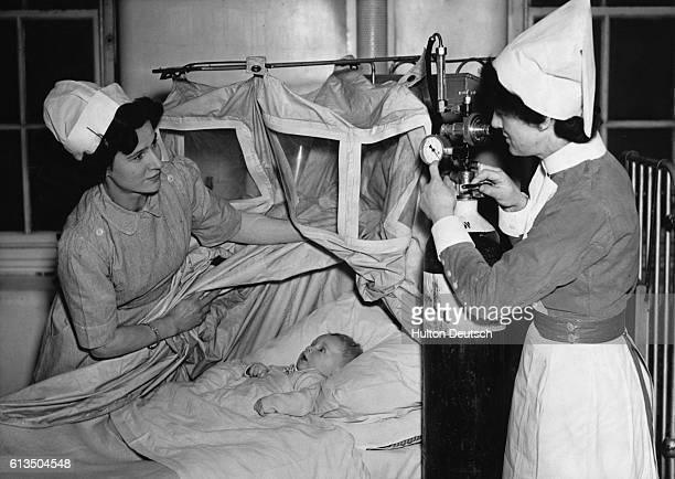 Volunteers in London's Paddington Hospital adjust the oxygen tent over an infants bed