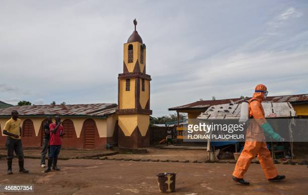 A volunteers in protective suit walks on his way to spray disinfectant onto the walls of homes that were inhabited by people who died of Ebola in...