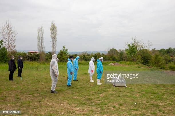 Volunteers in protective suits pray before the body of a COVID-19 victim at a funeral on April 10, 2020 in Qaem Shahr, Iran. The Coronavirus pandemic...