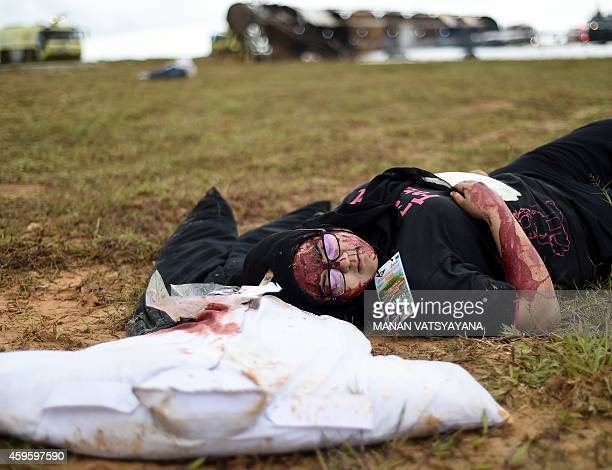 Volunteers inact a mock scene of an airplane crashsite during an emergency drill at the Kuala Lumpur International Airport in Sepang on November 26...