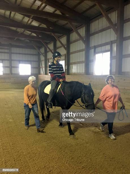 Volunteers Jan Lauwers and Liz Klemenswicz with Giant Steps help rider Waqas Kahn during a program at Rich Harvest Farms near Sugar Grove Ill
