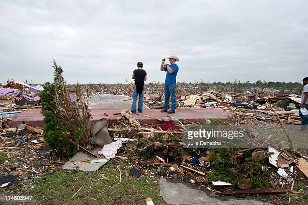 Volunteers Kelly Woods and Brian Jeffus from Broken Arrow Oklahoma take a moment to absorb the enormity of the disaster after a massive tornado...