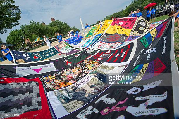 Volunteers lay out the AIDS Quilt on the National Mall July 23 2012 as part of the 19th International AIDS Conference in Washington DC The conference...