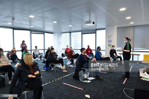 Volunteers learn how to administer an injection during a vaccinator training day lesson ran by the St John's Ambulance in Canary Wharf, east London,...