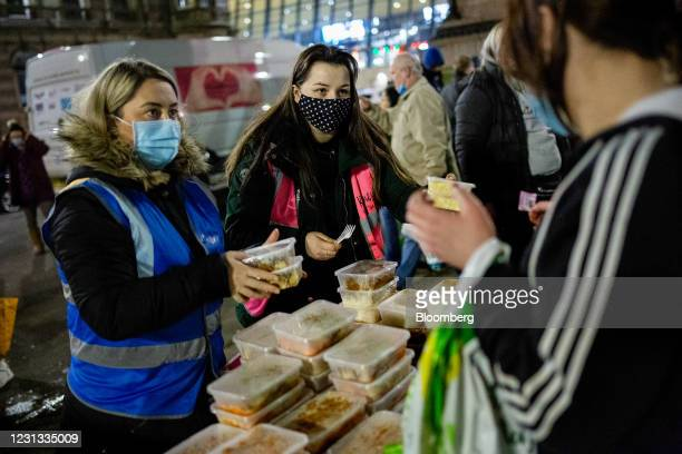 Volunteers, left, from the Kindness Homeless Street Team charity distribute food and essentials at George Square in Glasgow, U.K., on Monday, Feb....