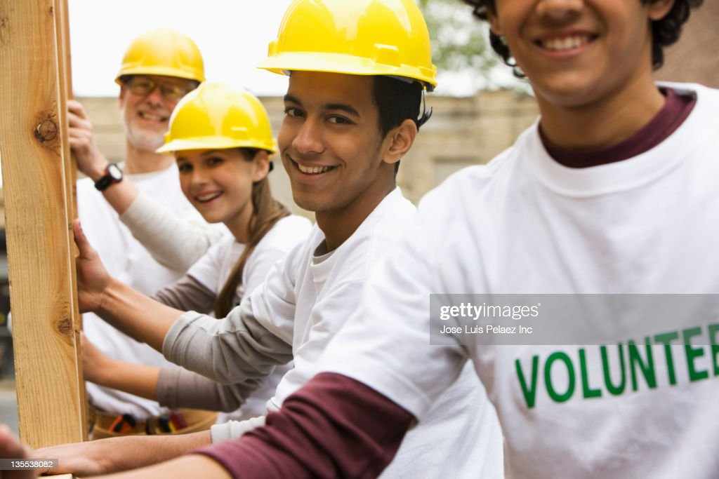 Volunteers lifting construction frame together : Stock Photo