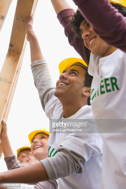 volunteers lifting construction frame together - multiculturalism stock pictures, royalty-free photos & images
