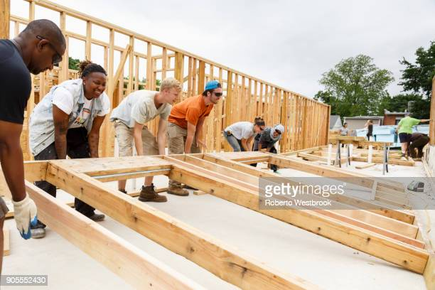 volunteers lifting framed wall at construction site - community outreach stock pictures, royalty-free photos & images