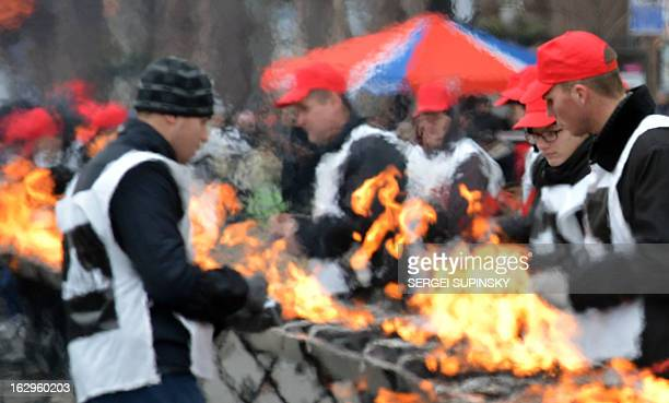 Volunteers light a fire on a huge brazier as they prepare to cook a shashlyk or skewer of meat measuring 1506 meters in length in the Ukrainian...