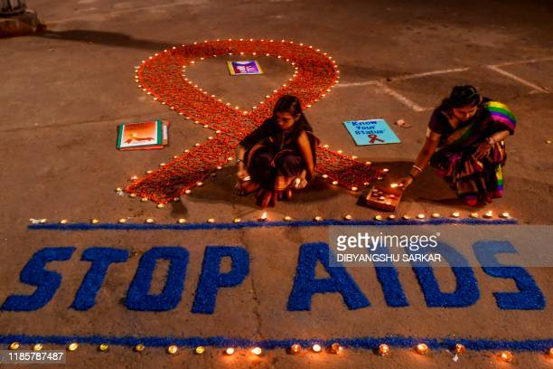 Volunteers light candles forming the shape of a red ribbon and a message reading 'Stop AIDS' during an awareness event on the occasion of the 'World...