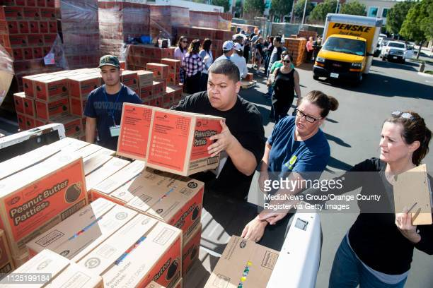 Volunteers load Peanut Butter Patties into the back of a truck from Orange Troop 2885 during the Girl Scout Cookie Mega Drop at the Anaheim Business...