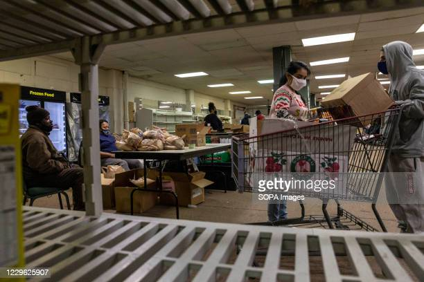 Volunteers load up shopping carts with food items to be distributed to the people. Neighbourhood Health Association partners with Greater Grace...