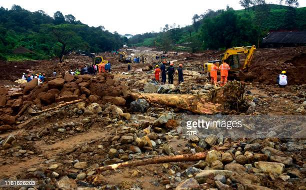 Volunteers local residents fire force officials and members of National Disaster Response Force search for survivors following landslides at...