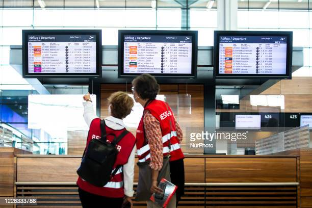 Volunteers look at a display with flight information during a test run at Berlin Brandenburg Airport 'Willy Brandt' ahead of its opening, planned for...