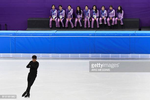 TOPSHOT Volunteers look at an athlete practicing on the men single skating in the Gangneung Ice Arena during the 2018 Pyeongchang Winter Olympic...