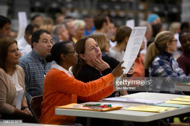 Volunteers look at ballots during a hand recount at the Supervisor of Elections Service Center on November 16 2018 in Palm Beach Florida After...