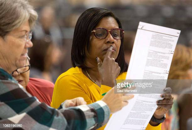Volunteers look at ballots during a hand recount at the Supervisor of Elections Service Center on November 18 2018 in Palm Beach Florida Sen Bill...