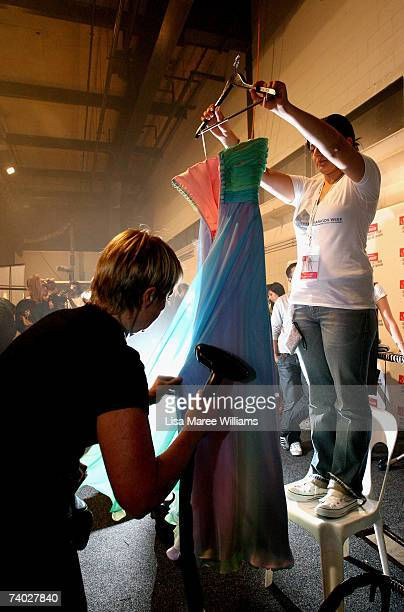 Volunteers make the final touches to a design by Alex Perry prepare backstage ahead of his catwalk show on day one of Rosemount Australian Fashion...