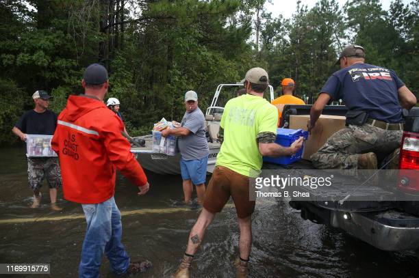 Volunteers maneuver food and first aid items onto a truck that will be delivered to the First Baptist Church in Hampshire on highway 124 on September...