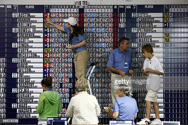 Volunteers manually update a scoreboard inside the media center tent during the Barclays Classic golf tournament at Westchester Country Club in Rye...
