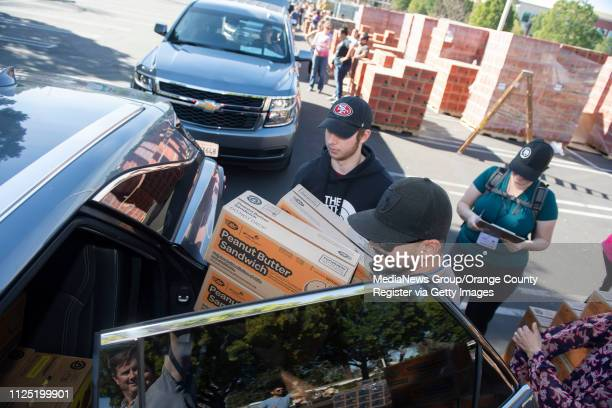 Volunteers Michael Gorecki of Orange front and Michael Puskas of Anaheim Hills load Peanut Butter Sandwiches into a car for Anaheim Hills' Troops...