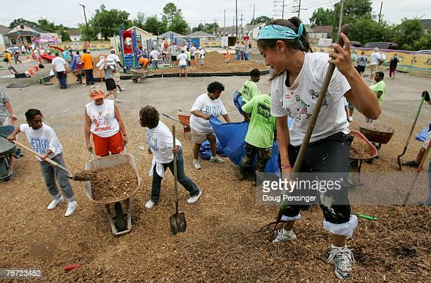 Volunteers move mulch during a playground building at the JW Johnson Elementary School prior to the ArenaBowl XXI Kickoff Press Conference July 26...