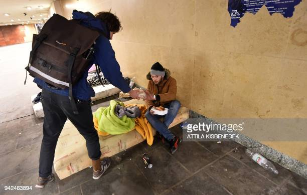 Volunteers of a civil society organisation called the Budapest Bike Maffia distribute sandwiches to homeless people on March 26 2018 in the capital...