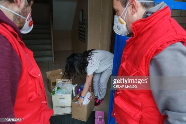 Volunteers of Caritas the Spanish Catholic Church's confederation of the social and charitable action organisations leave boxes of food and basic...