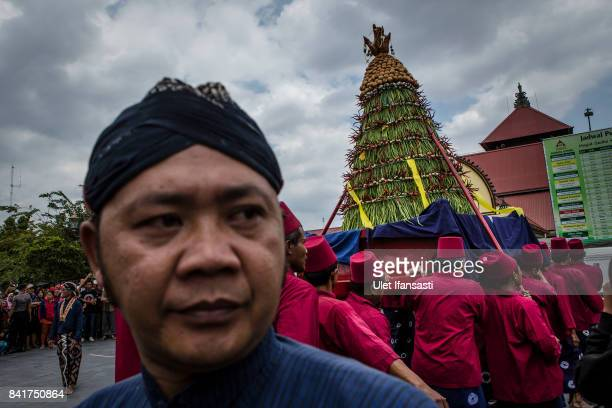 Volunteers of Kraton Palace known as 'Abdi Dalem' carry 'Gunungan' from Kraton Palace to the Great Mosque Kauman during the Grebeg ritual as part of...