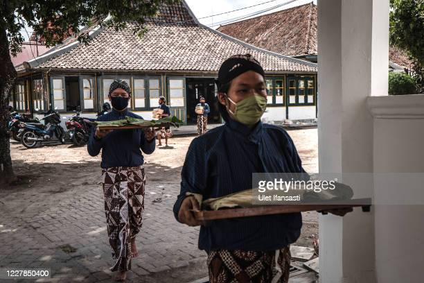 Volunteers of Kraton Palace of Yogyakarta, known as 'Abdi Dalem' carry meats to distribute during celebrations for Eid al-Adha or the 'Festival of...