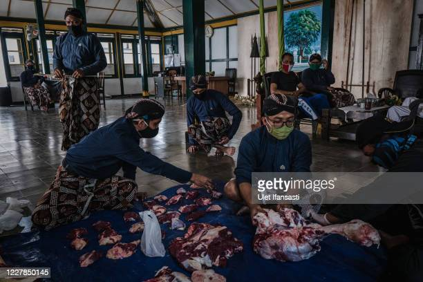 Volunteers of Kraton Palace of Yogyakarta, known as 'Abdi Dalem' cut meat to distribute during celebrations for Eid al-Adha or the 'Festival of...