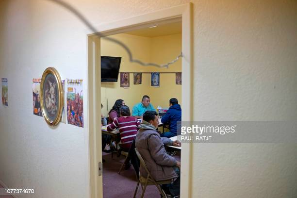 Volunteers of 'Project Oak Tree' assist migrants with booking plane tickets inside the church hall of the Basilica of San Albino in Mesilla New...
