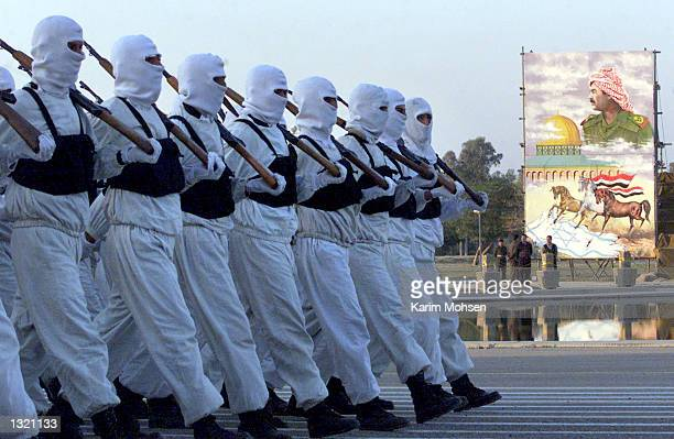 Volunteers of the Al Quds Agrauation parade march by a portrait of Iraqi President Saddam Hussein June 10 2001 in Baghdad Iraq The 12 division army...