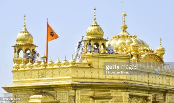 Volunteers of the Guru Nanak Nishkam Sewak Jatha from the United Kingdom, work on cleaning the gold plating on the Golden Temple on March 12, 2020 in...