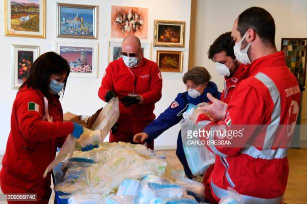 Volunteers of the Italian Red Cross prepare protective masks which will be distribute for free to Florence residents to contain the spread of the...